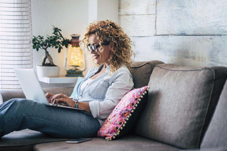 Smiling woman using laptop on couch at home