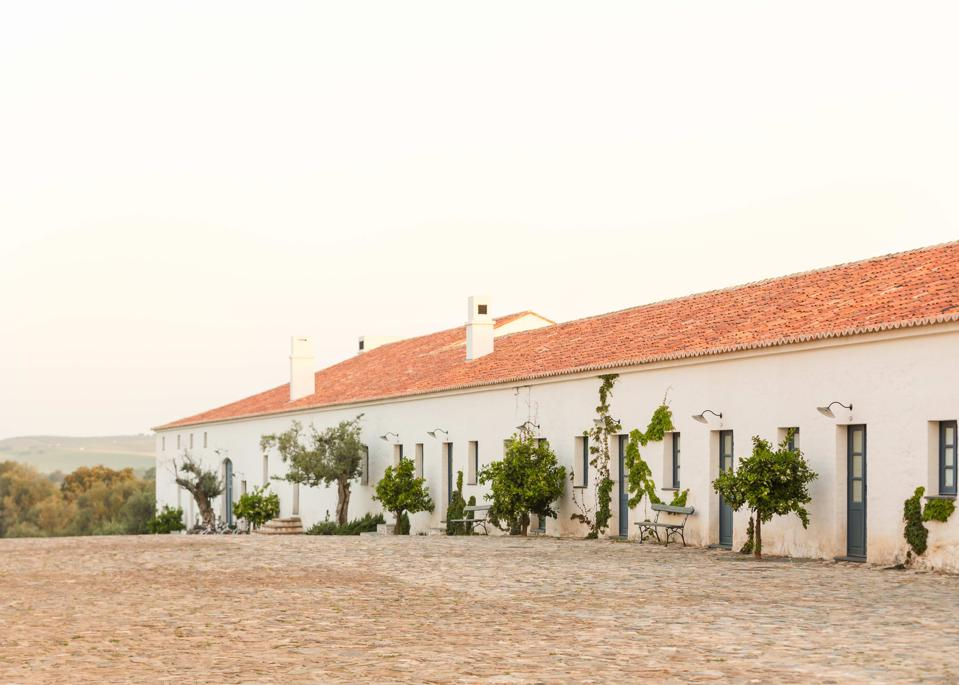 The sun is setting and the sky is pink behind a farmhouse building in the Alentejo