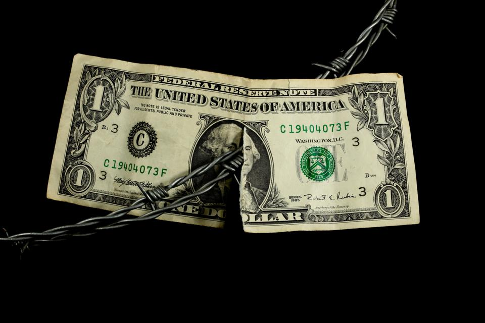Barbed wire dividing a old weathered and ripped dollar bill
