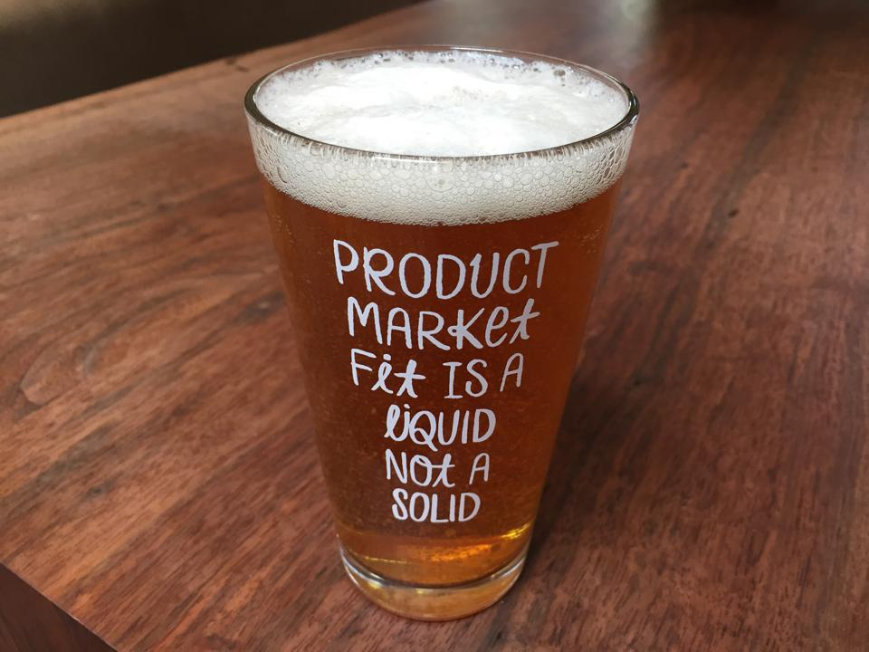 A clear pint glass full of beer with the words ″Product market fit is a liquid not a solid″ etched on the front.
