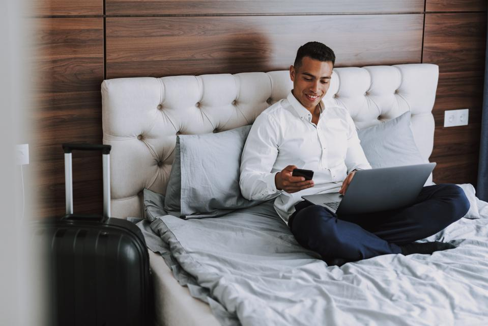 Cheerful man is using modern technologies in hotel room
