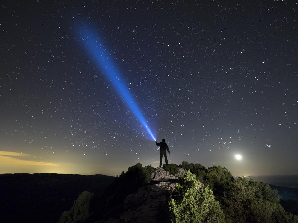 Silhouette of a man on the top of a mountain at night holding a beam of light up at the sky of stars