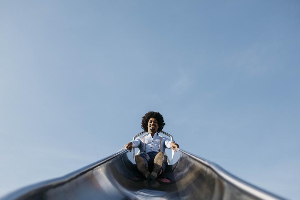 Smiling man sitting on slide