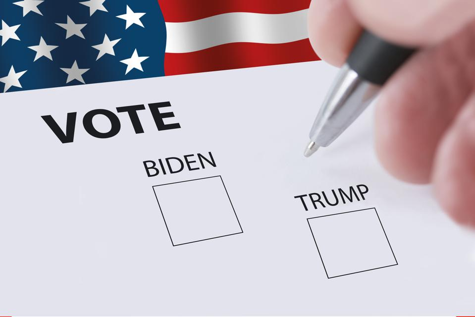2020 presidential vote ballot with a blurred hand holding a pencil and check boxes for voting for Biden or Trump.