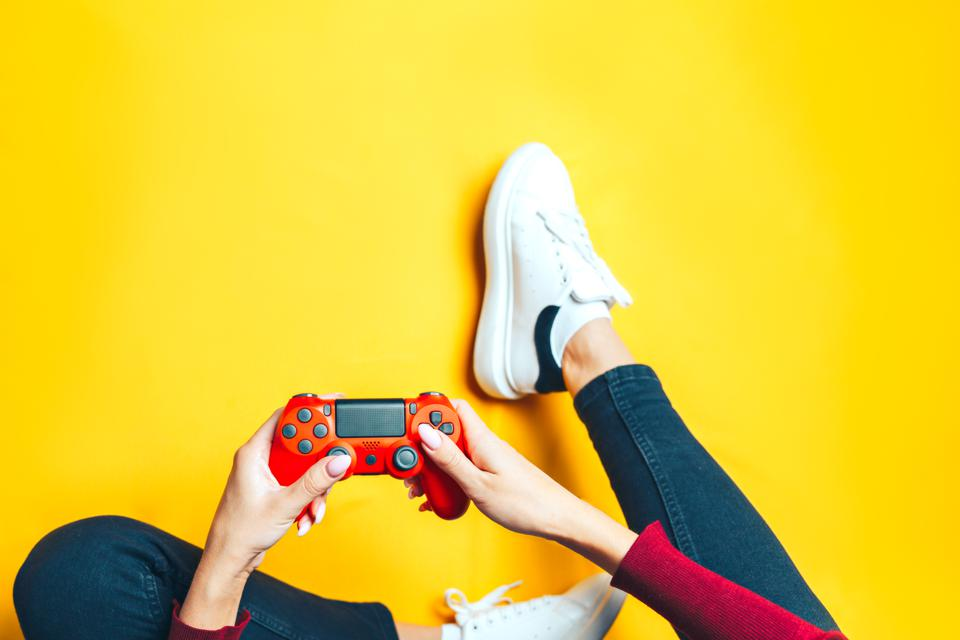 Young woman playing with two game controller on yellow background.