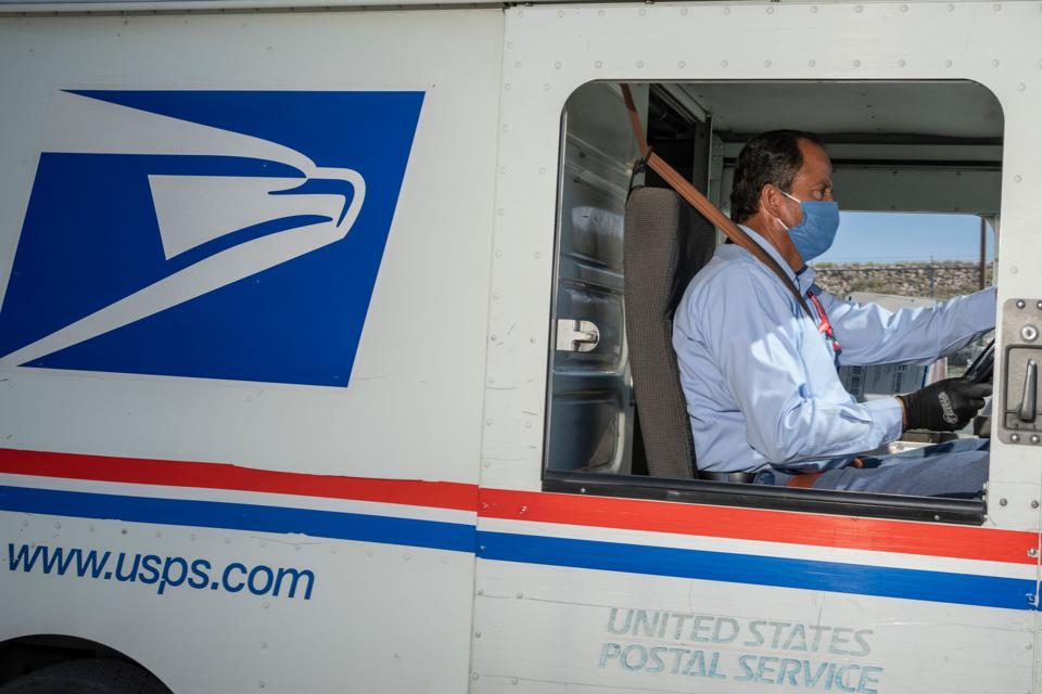 United States Postal Service mail carrier Frank Colon, 59, departs on his delivery route at the Remcon Circle Post Office on April 30, 2020. (Photo by Paul Ratje / AFP) (Photo by PAUL RATJE/AFP via Getty Images)