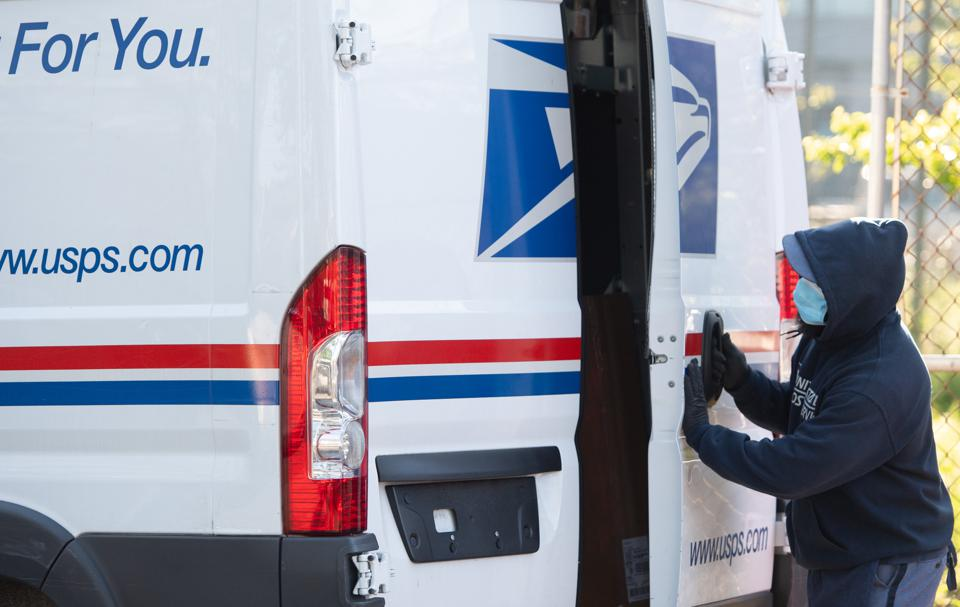 A mailman wearing a mask and gloves to protect himself and others from COVID-19, closes the doors to a postal truck after loading it with packages in Washington, D.C. on April 16, 2020.