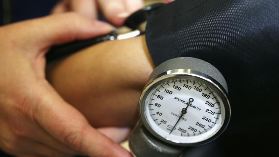National Blood Service nurse checks blood pressure and pulse of donor using sphygmomanometer and stethoscope