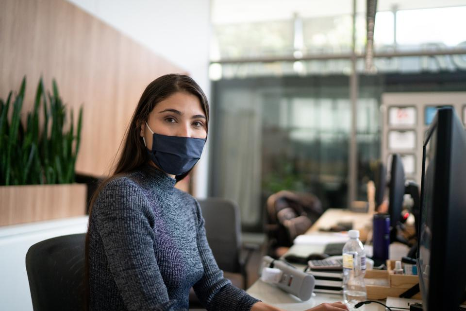 A lobby receptionist wearing a face mask