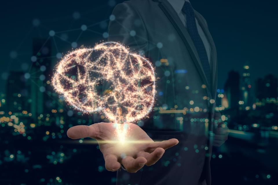 Double exposure of Businessman hand holding the brain base on sparkle over photo blurred of cityscape background, Artificial Intelligence or AI concept