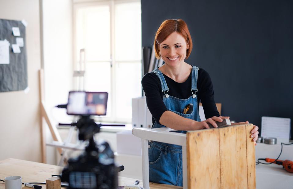 Woman vlogger or blogger making video about old furniture restoration.