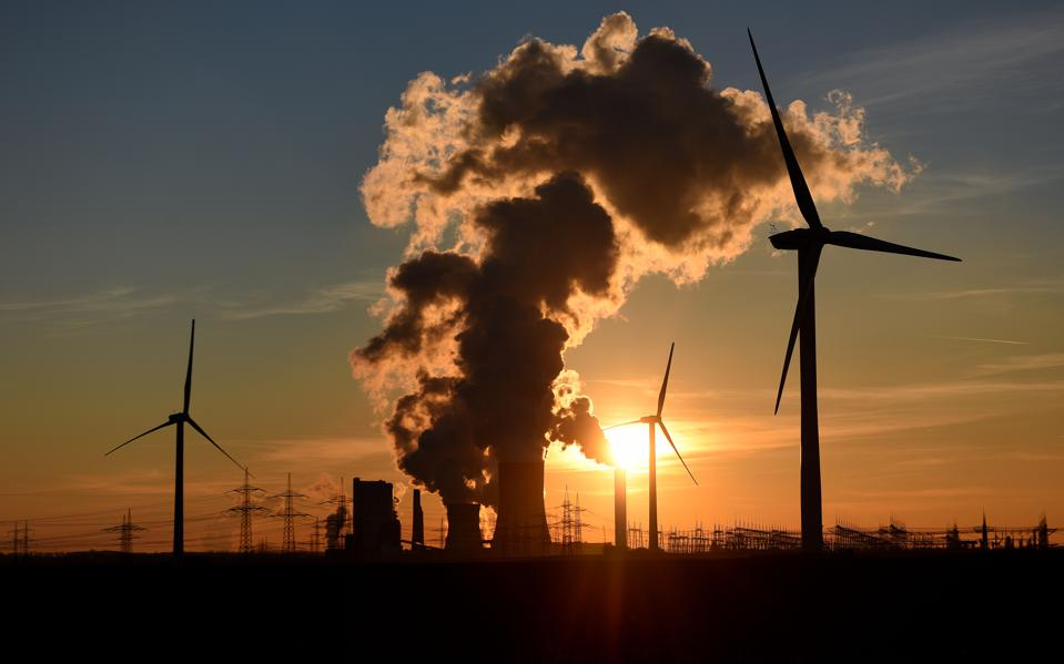 Electricity pylons, wind turbines stand beside coal-fired power plant