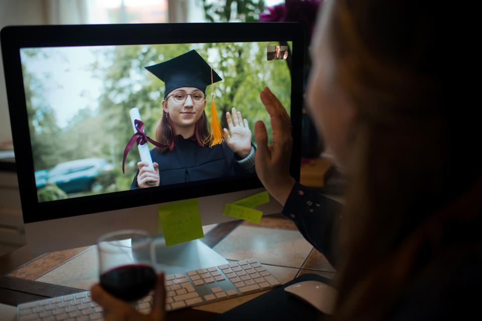 Teenage girl wearing graduation gown and cap greeting her relative or friend on video call