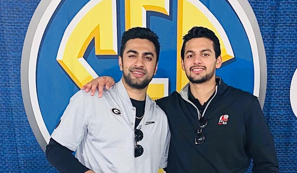 Two brothers dressed in sports gear in front of an SEC emblem.