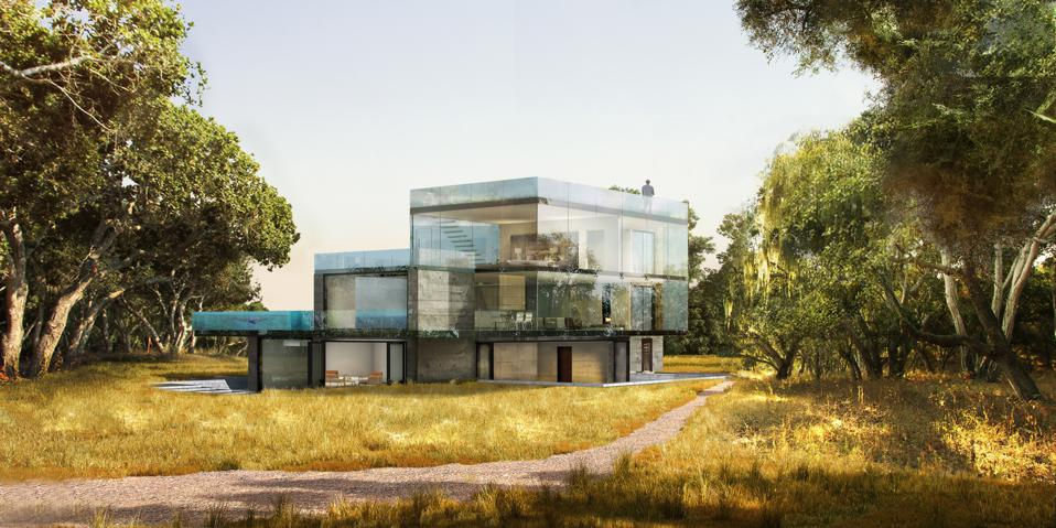 A glass-enclosed concept home surrounded by trees.