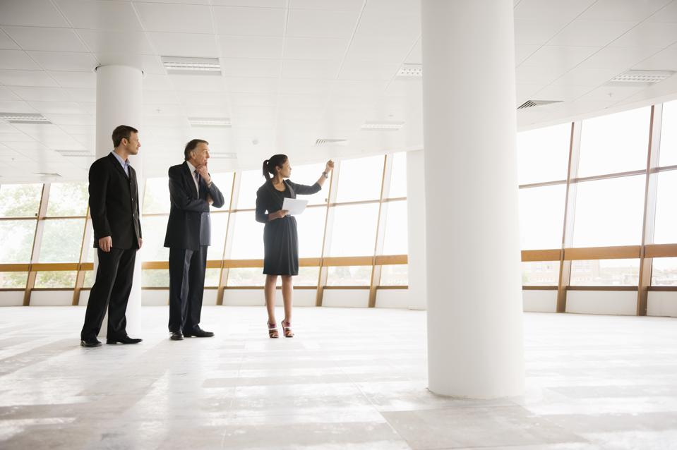 three professionals standing in large open room