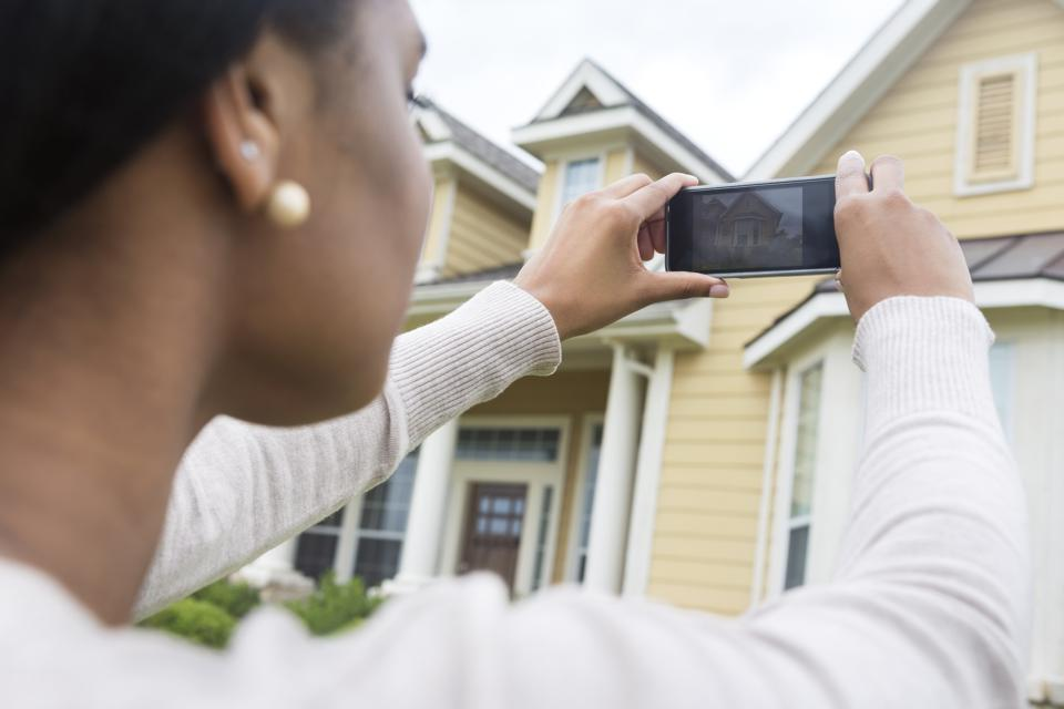 Young woman taking photo of new home with smart phone