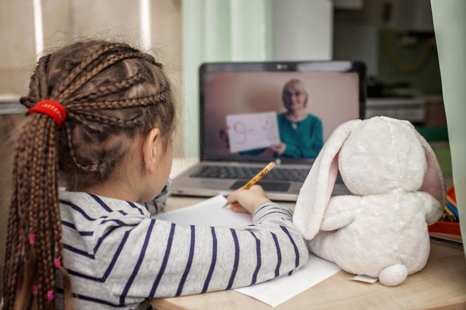 Pretty stylish schoolgirl studying math during her online lesson at home, self-isolation