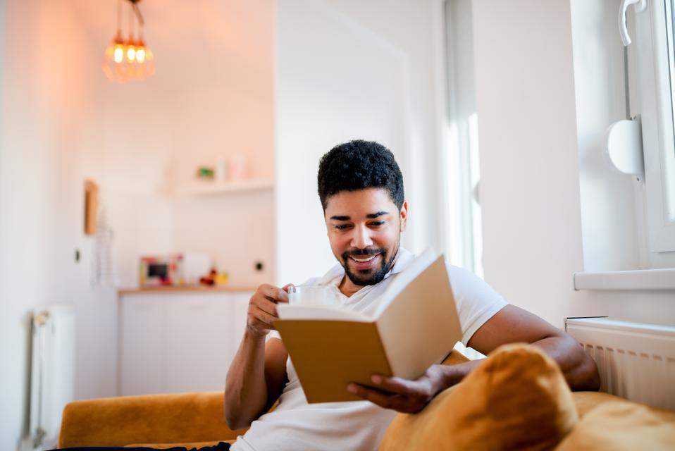 Man sitting on sofa reading book.