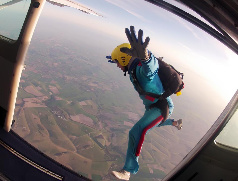 Parachutist jumps through the door of the plane