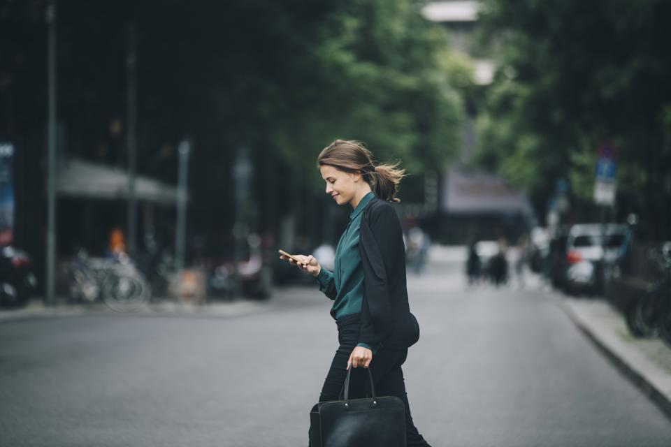 Confident businesswoman using smart phone while crossing street in city