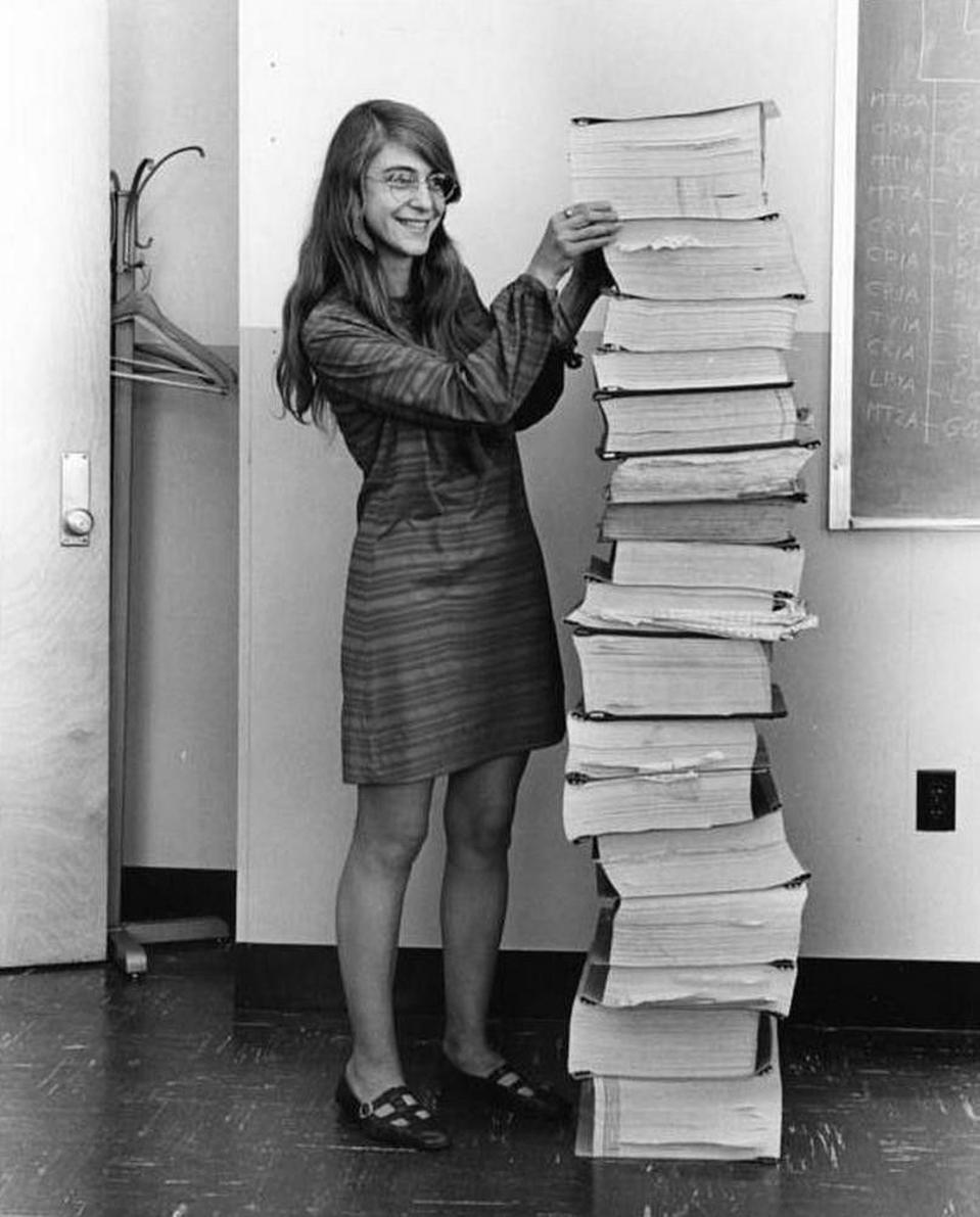 Margaret Hamilton next to stack of Apollo code listings.
