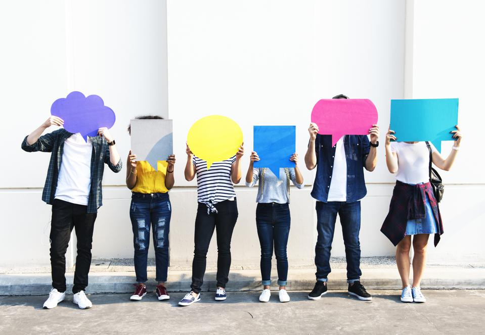 Young adult friends holding up copy space placard thought bubbles