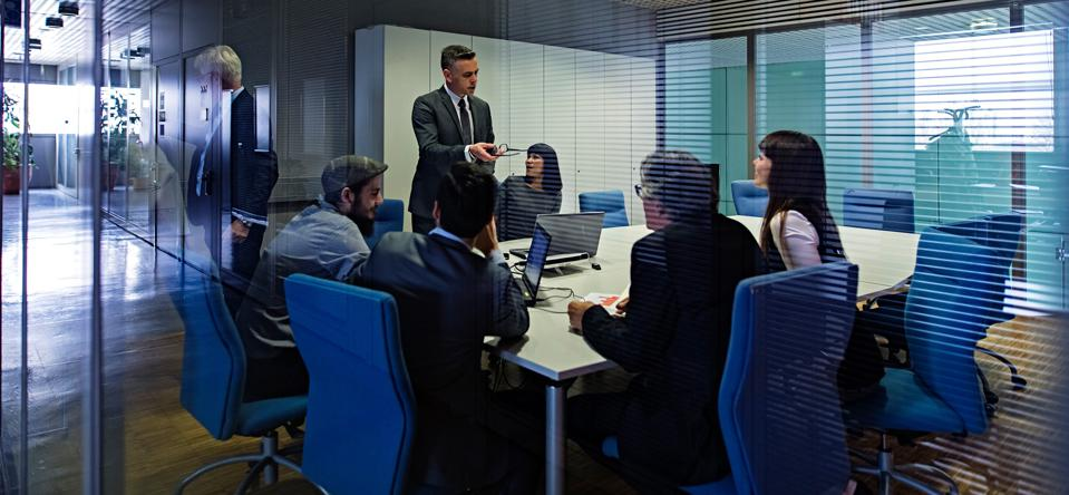 Six men and women around a meeting table in a conference room.