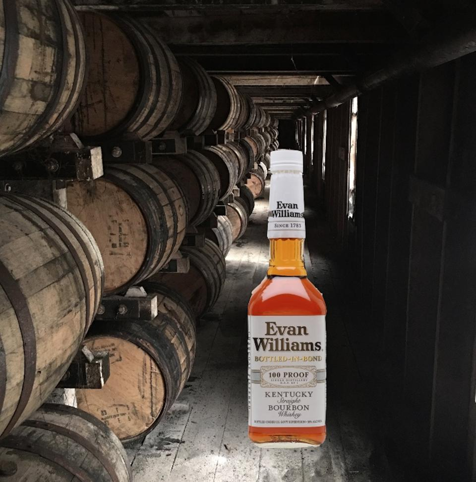 A bottle of Kentucky straight bourbon standing in a rickhouse next to barrels of whiskey