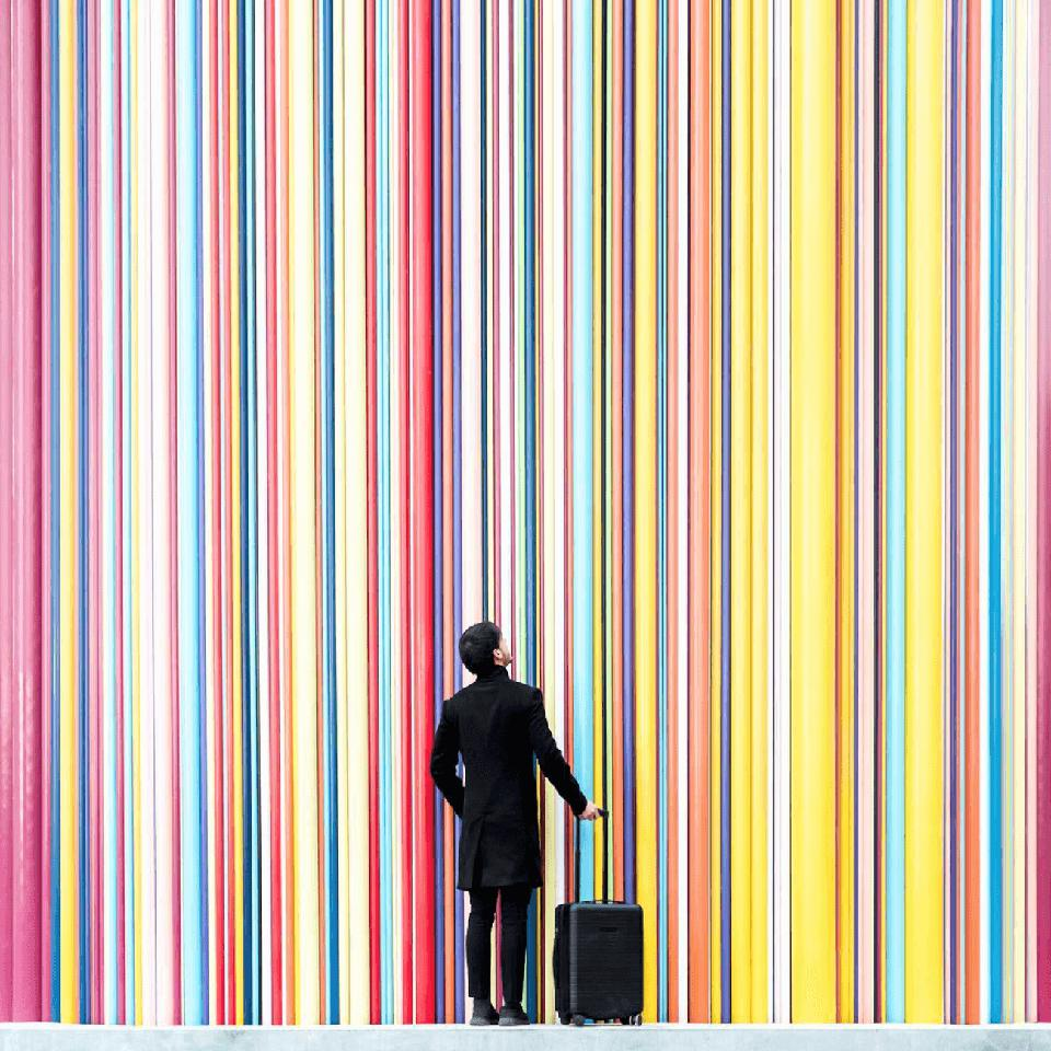 Daniel Rueda stands in front of the rainbow-colored striped facade of a building.