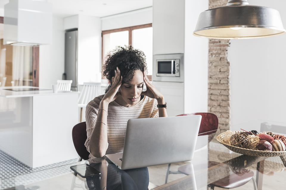 Worried woman using laptop computer at home