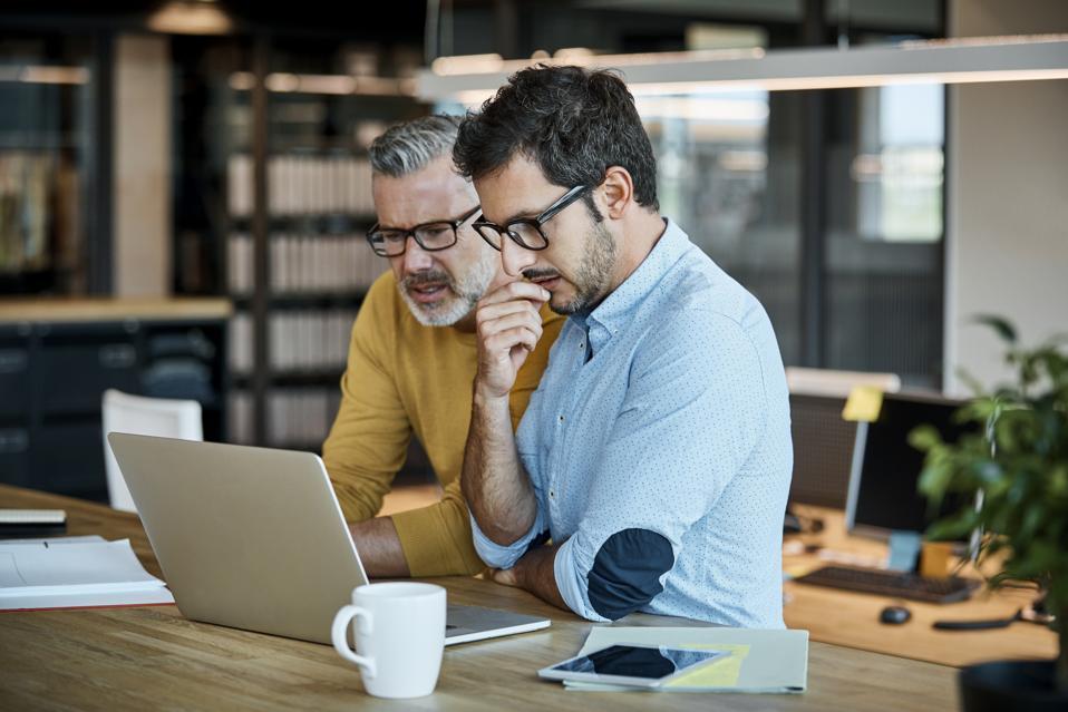 Businessmen using laptop at desk
