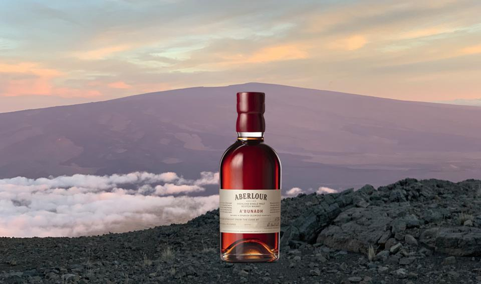 A bottle of burgundy-hued scotch with a mountain rising above the clouds in the background