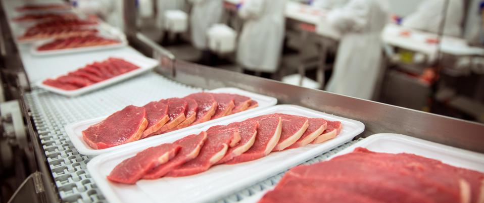 Thinly sliced meat on a conveyor belt in a processing plant.