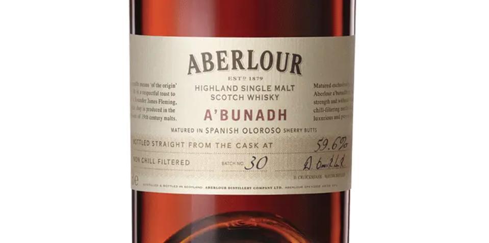 A label of A'bunadh single malt scotch whisky across a burgundy hued bottle of liquid