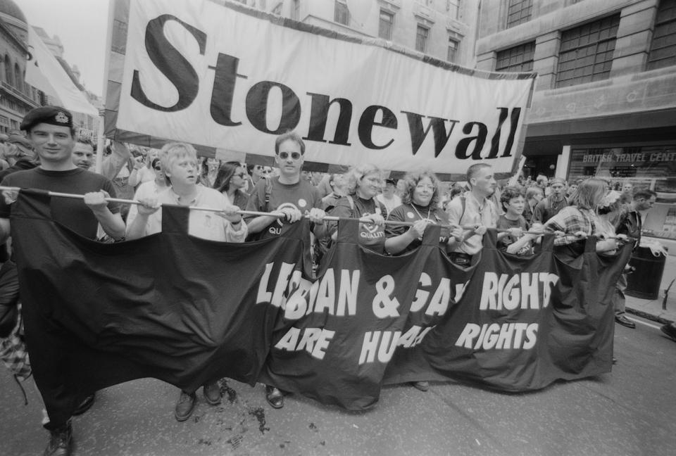 Protestors from lesbian, gay and bisexual rights charity Stonewall, carrying a banner reading 'Lesbian & Gay Rights are Human Rights' during the Gay Pride parade in London, England, United Kingdom, 6 July 1996. A large banner, reading 'Stonewall', is being carried in the background. (Photo by Steve Eason/Getty Images)