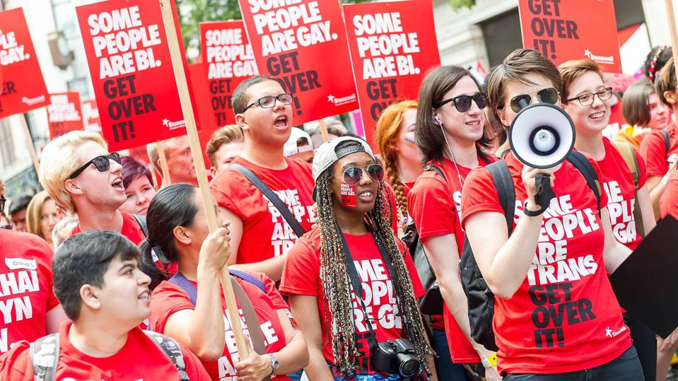 Stonewall volunteers march at London Pride in 2015, with campaign t-shirts, variations on the 'some people are gay get over it' campaign