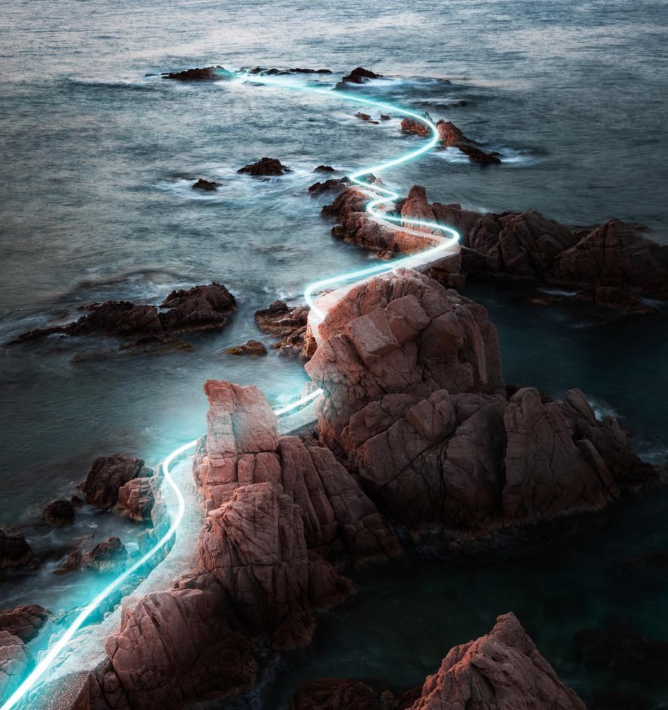 Blue light trail following footpath between the stunning coastline during sunrise.