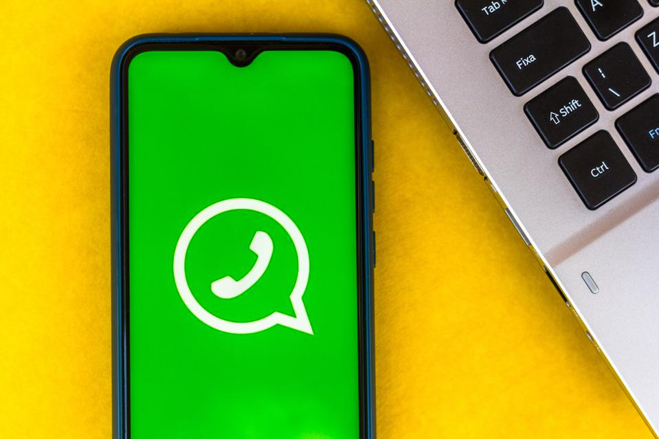 WhatsApp logo on a smartphone next to part of a laptop keyboard