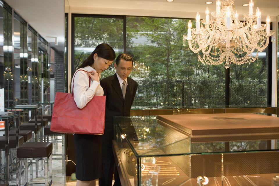 Two people looking at jewelry in display cabinets in a jewelry shop.