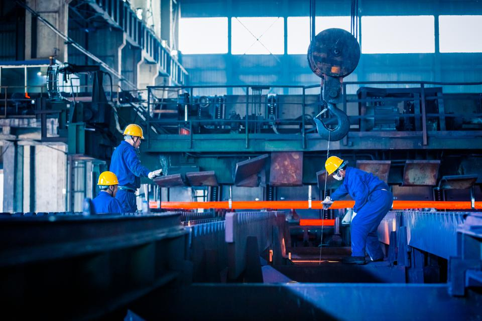 three factory workers in steel factory, moving orange girder on blue background. Workers distanced and wearing masks