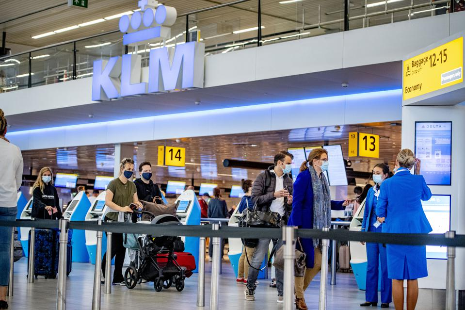 Travelers with face masks at the Schiphol airport in the Netherlands Europe during Covid