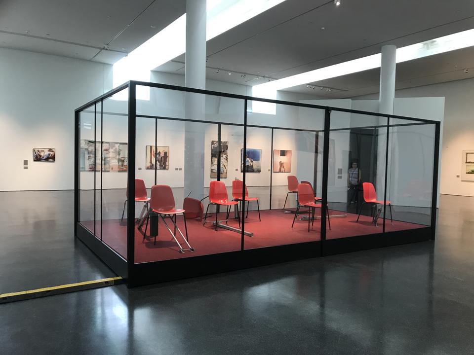art installation of red chairs in a glass box