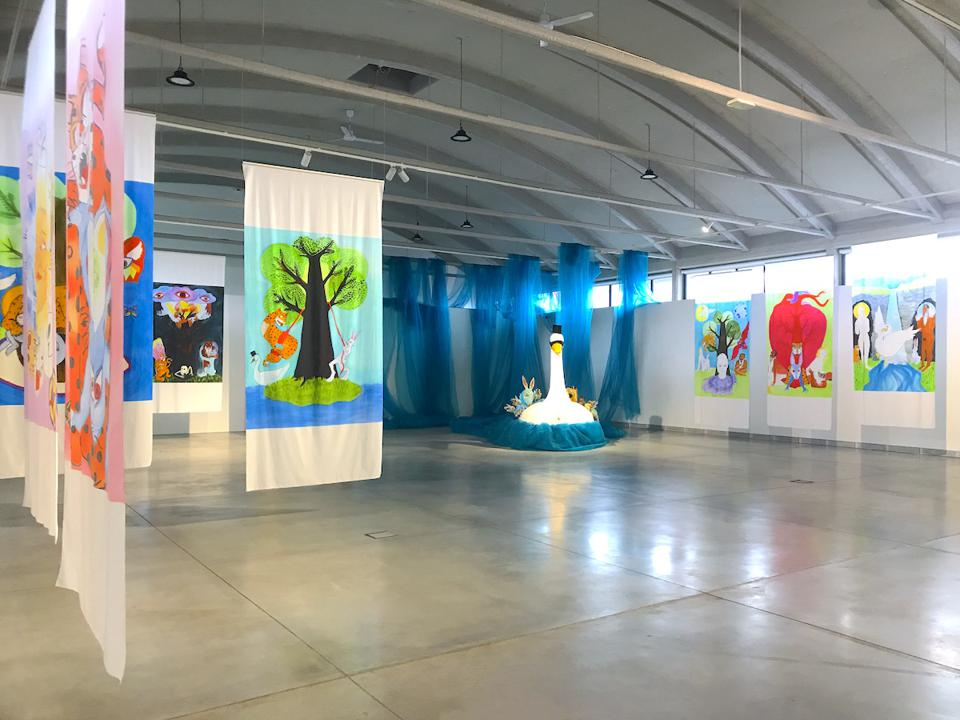 art gallery with colorful paintings on cloth and swan sculpture