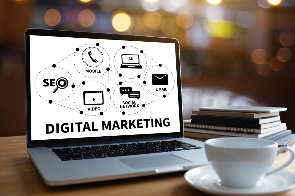 Laptop Displaying Digital Marketing Diagram With Books And Coffee Cup On Table
