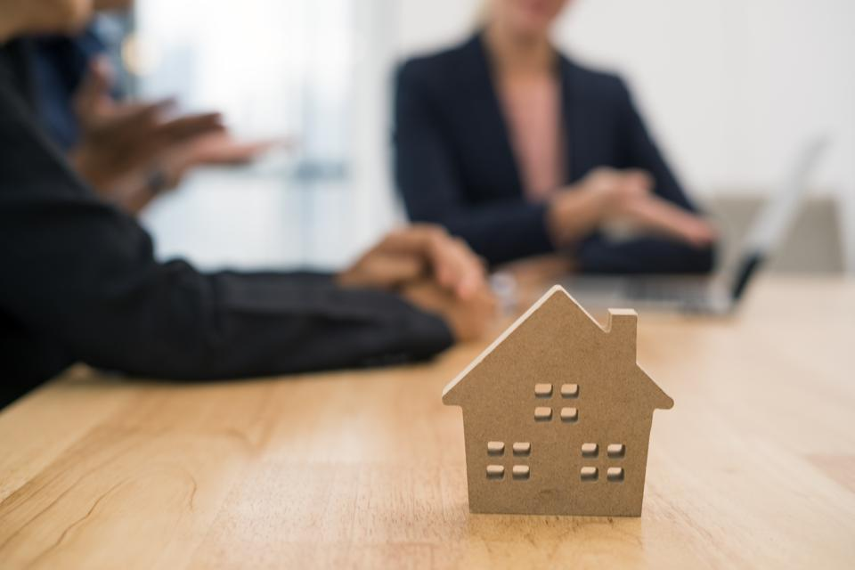 saleswoman presenting real estate to couple