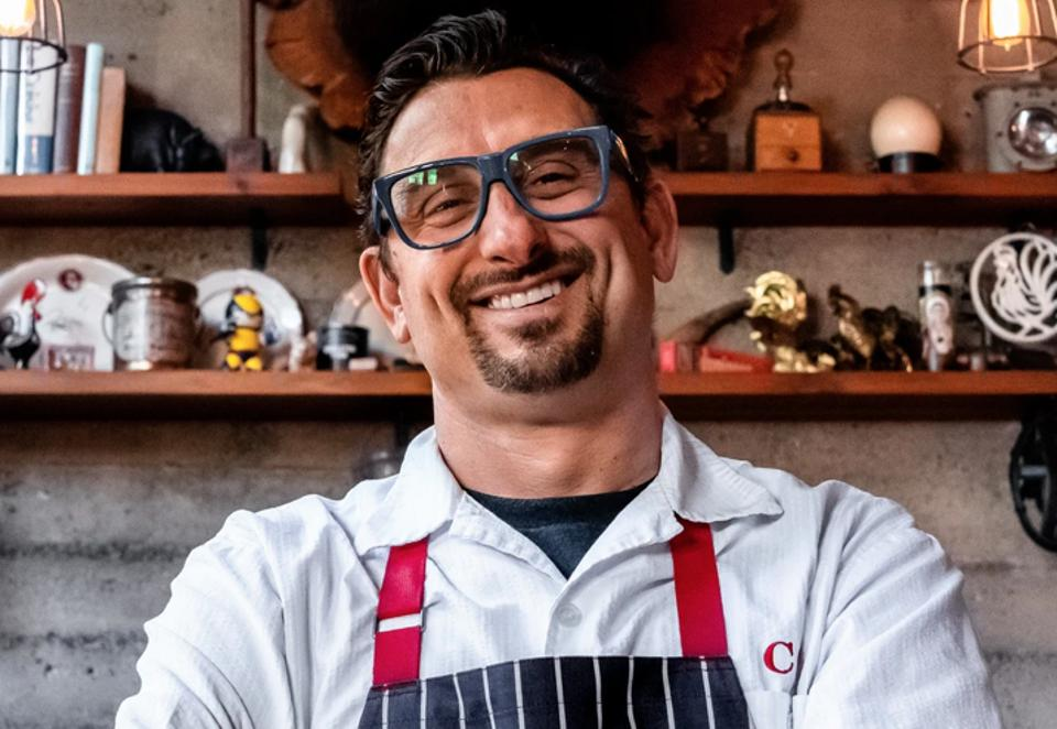 A chef in an apron smiles with a pair of large glasses on.