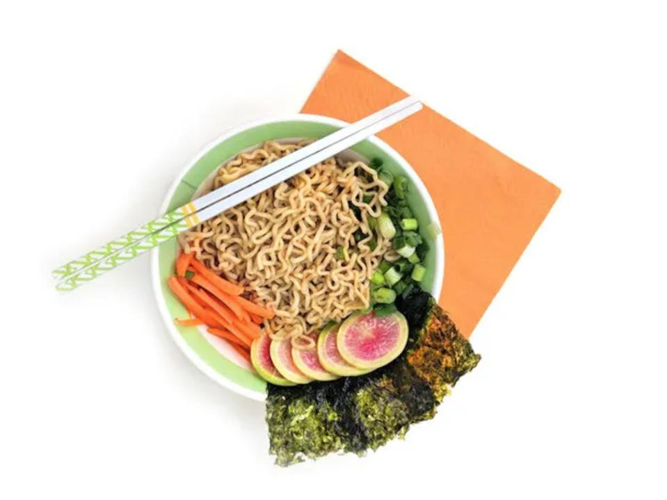 A bowl of noodle soup with seaweed and pickled vegetables as garnishes