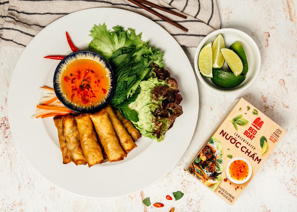 A package of concentrated Vietnamese dipping sauce sits next to a plate of spring rolls