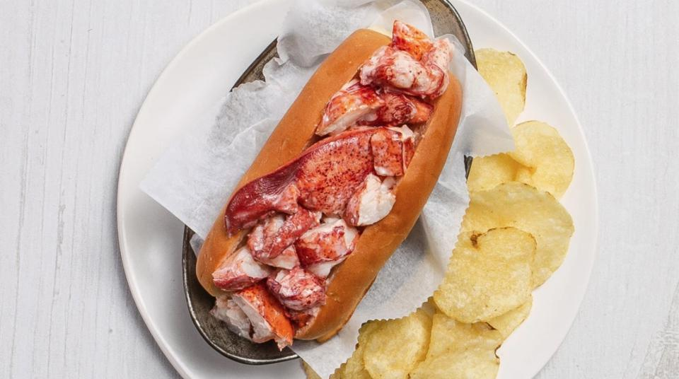 Lobster roll in a hot dog bun next to potato chips